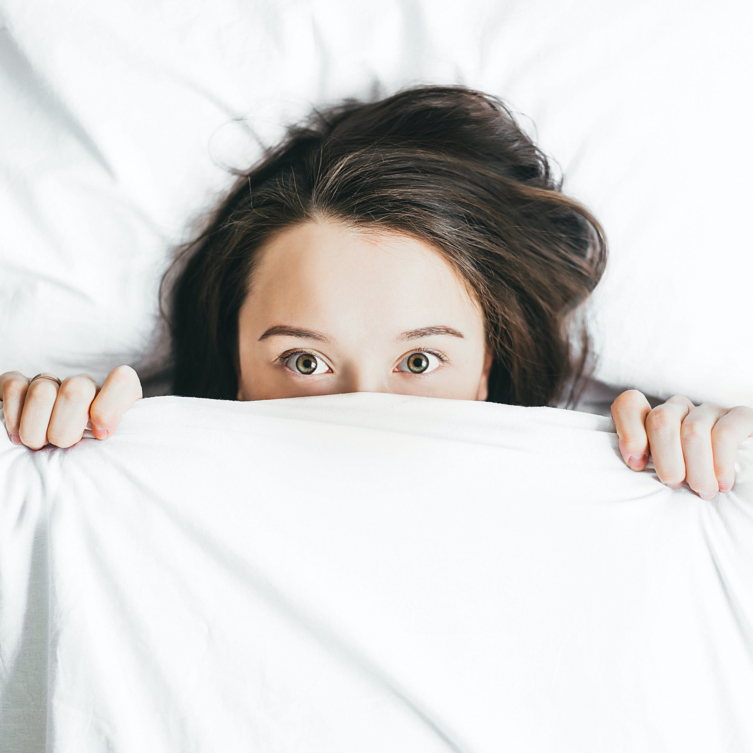 Woman in bed worried about signs of bedbugs